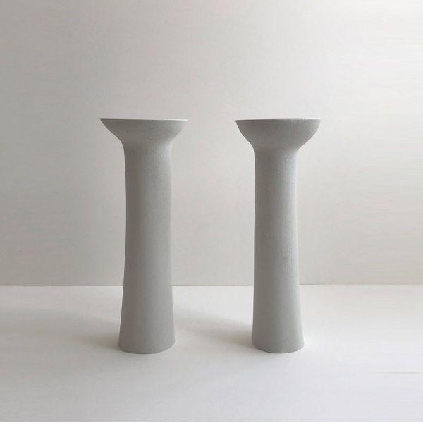 pair of pillar candlesticks by malgorzata bany grey background